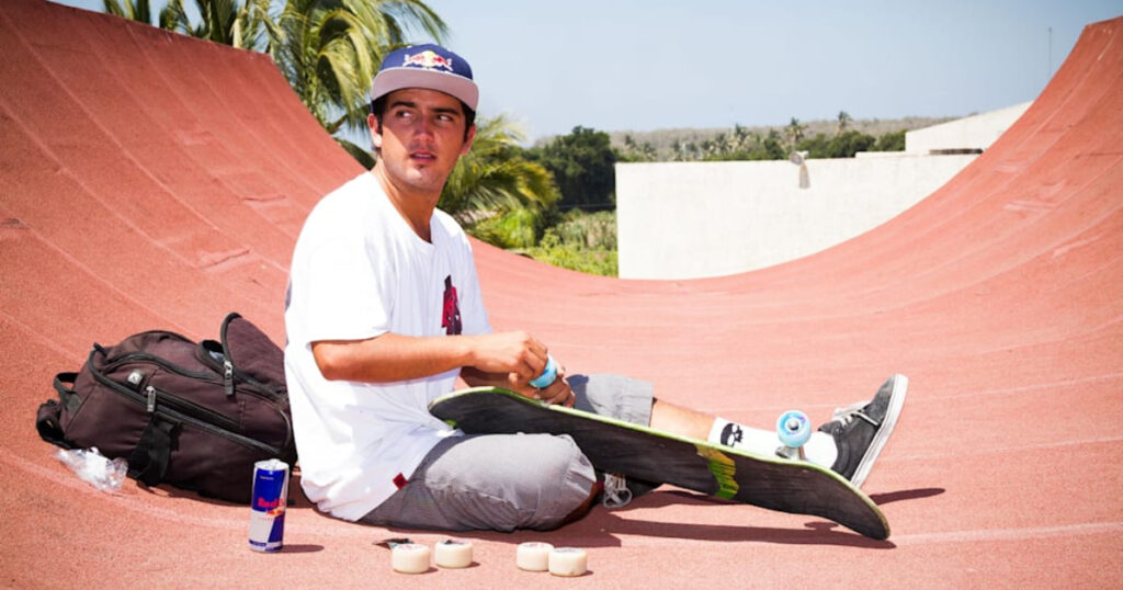 Skateboarder putting new wheels on his skateboard. From the essentials of a skateboarder's bag.