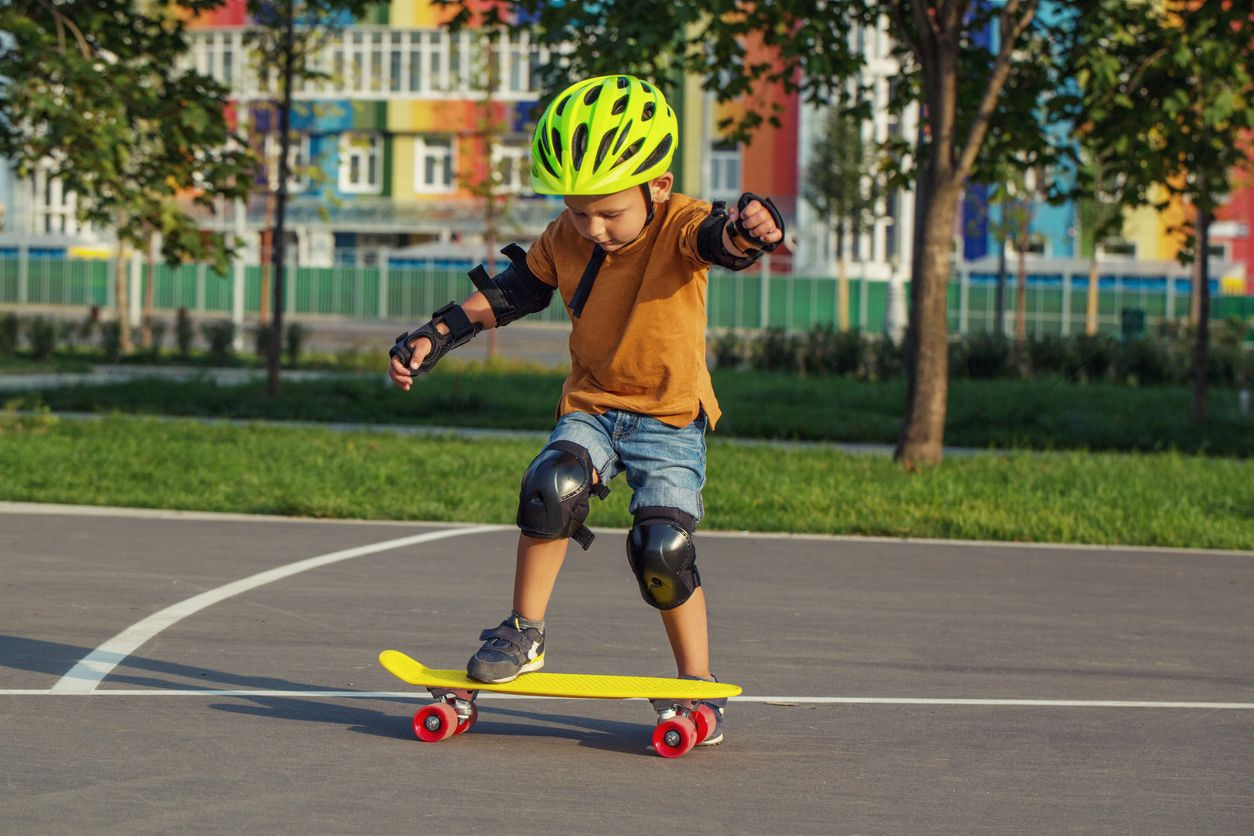 child learning how to skateboard on a penny board
